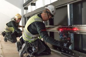 Tuulettuvan julkisivun rangan asennus laser kaksi miestä työkaluja