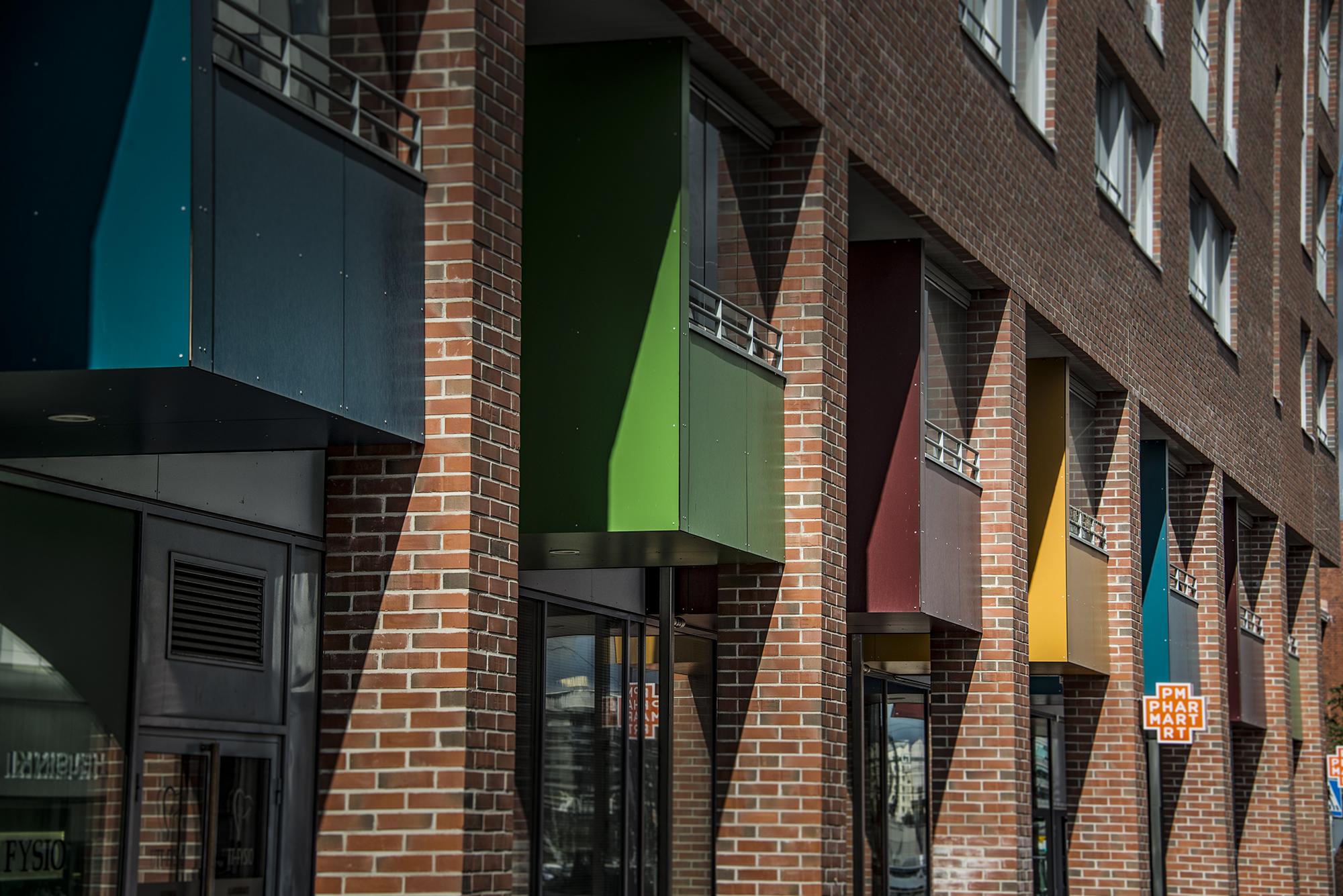 Trespa asennus parvekkeille: kuvassa värikkäitä parvekkeita kadun yläpuolella.